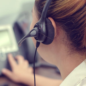 woman wearing headset answering help desk calls
