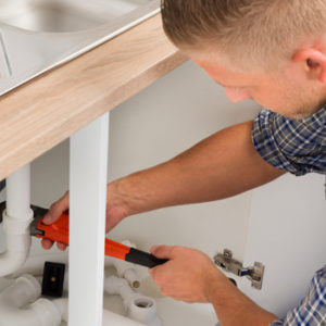 plumber working on a sink pipe