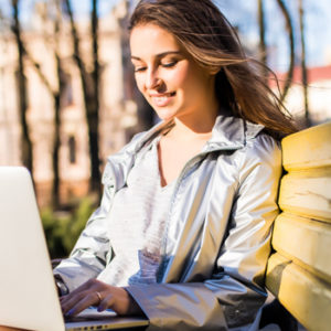 young woman on laptop in park